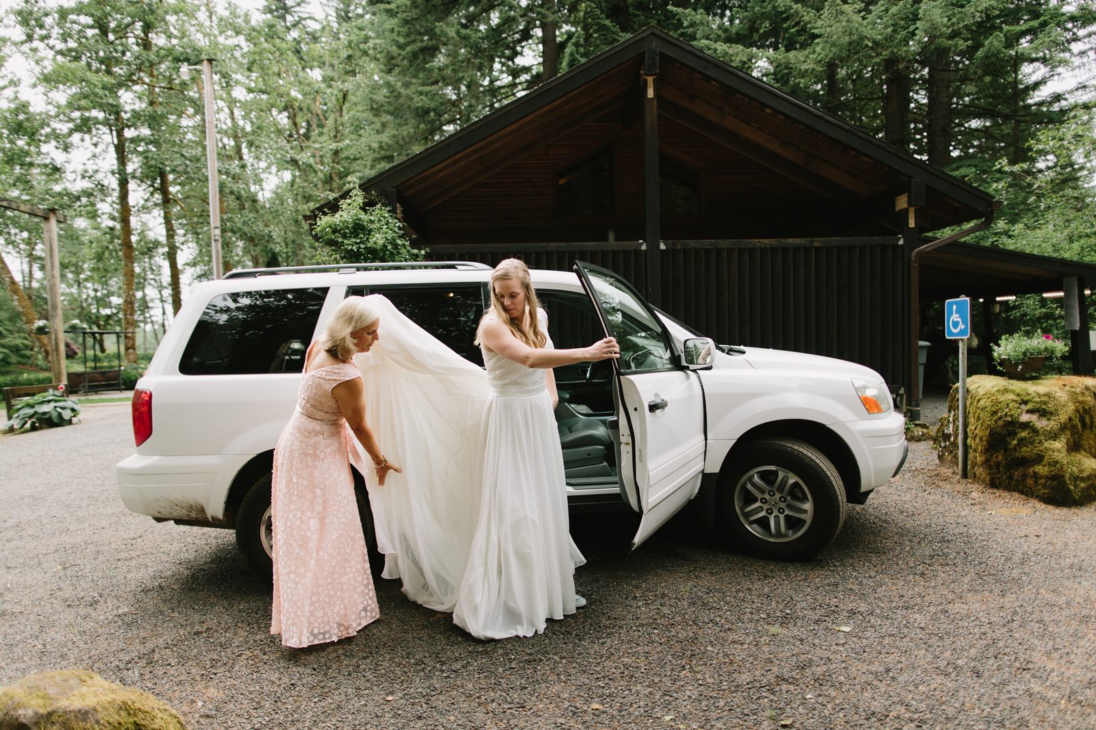 The bride's mother helps with her dress before the ceremony at Bridal Veil Lakes in Corbett, OR