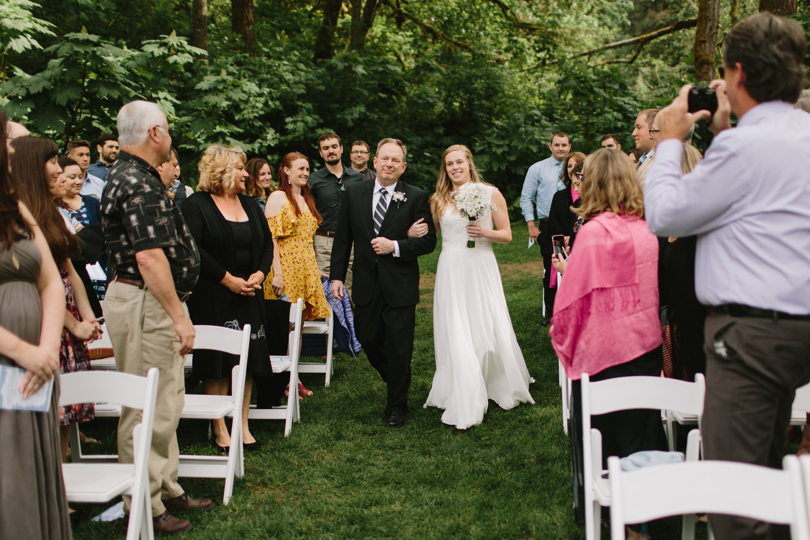The bride walks down the aisle with her father during the wedding ceremony at Bridal Veil Lakes in Corbett, OR