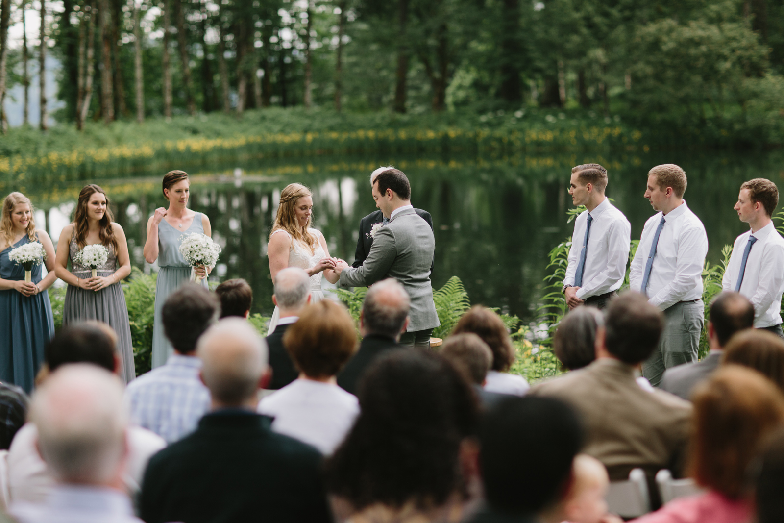 The bride puts a ring on the groom during the wedding ceremony at Bridal Veil