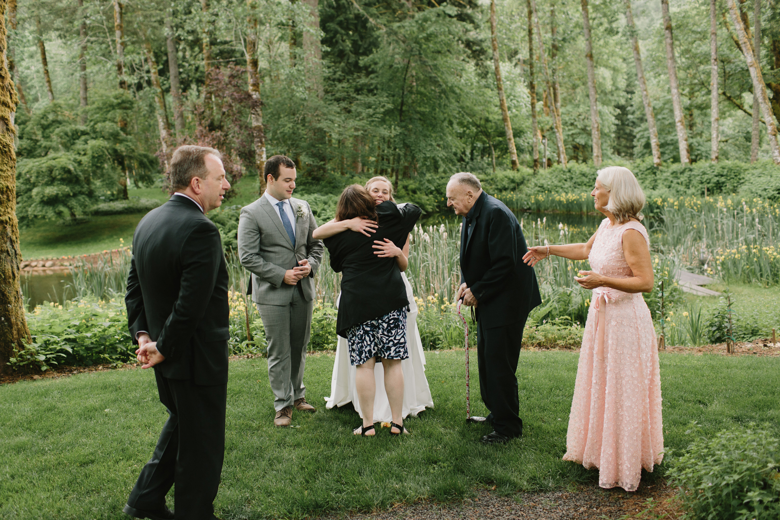 the bride and groom hug guests at their reception at Bridal Veil Lakes in Corbett, OR