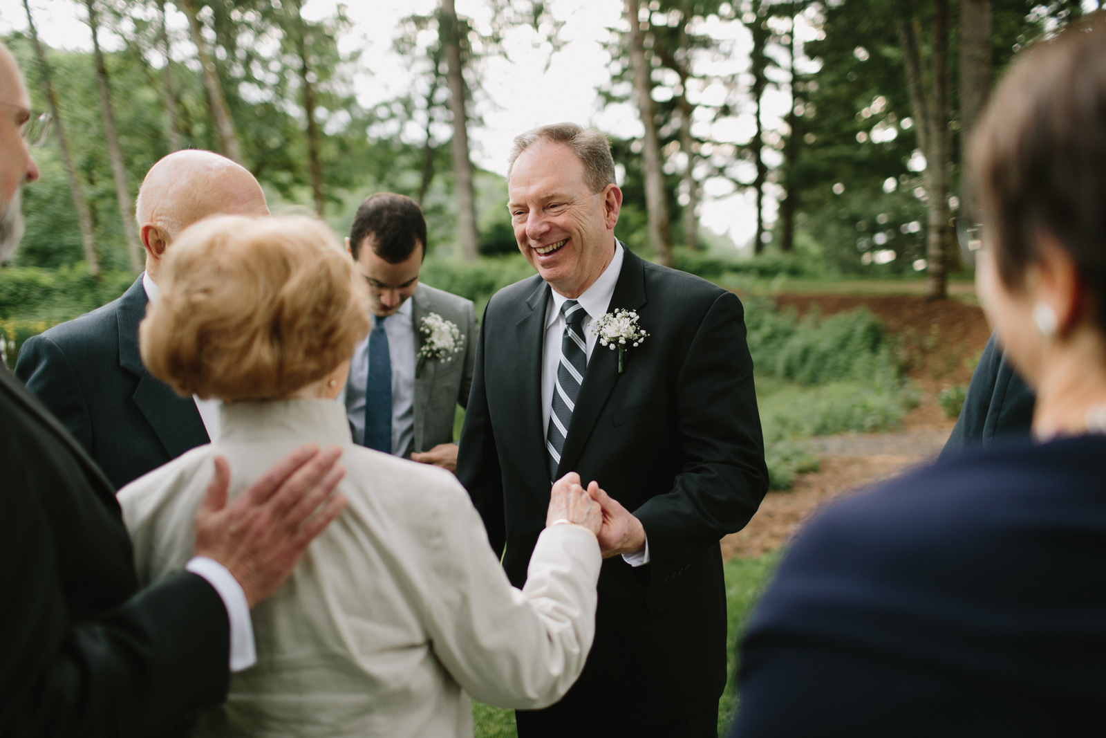 The father of the bride hugs guests at a wedding reception at bridal veil lakes in Corbett, OR