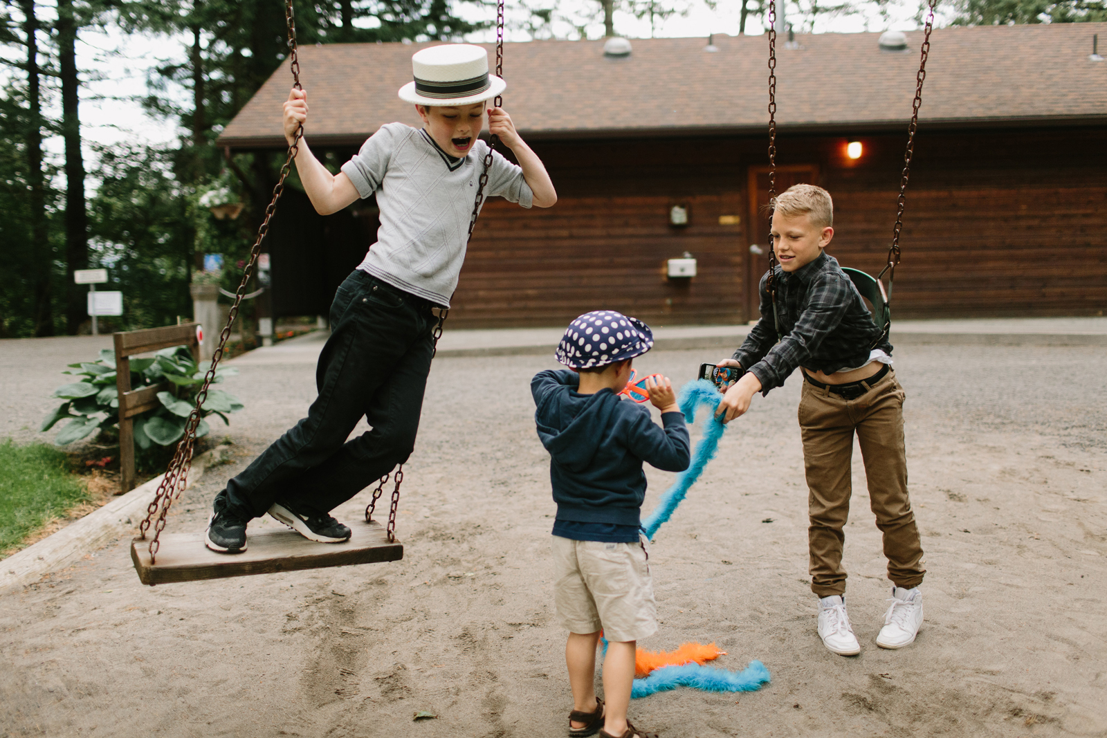 young guests swing with props at wedding reception at Bridal Veil Lakes in Corbett, OR