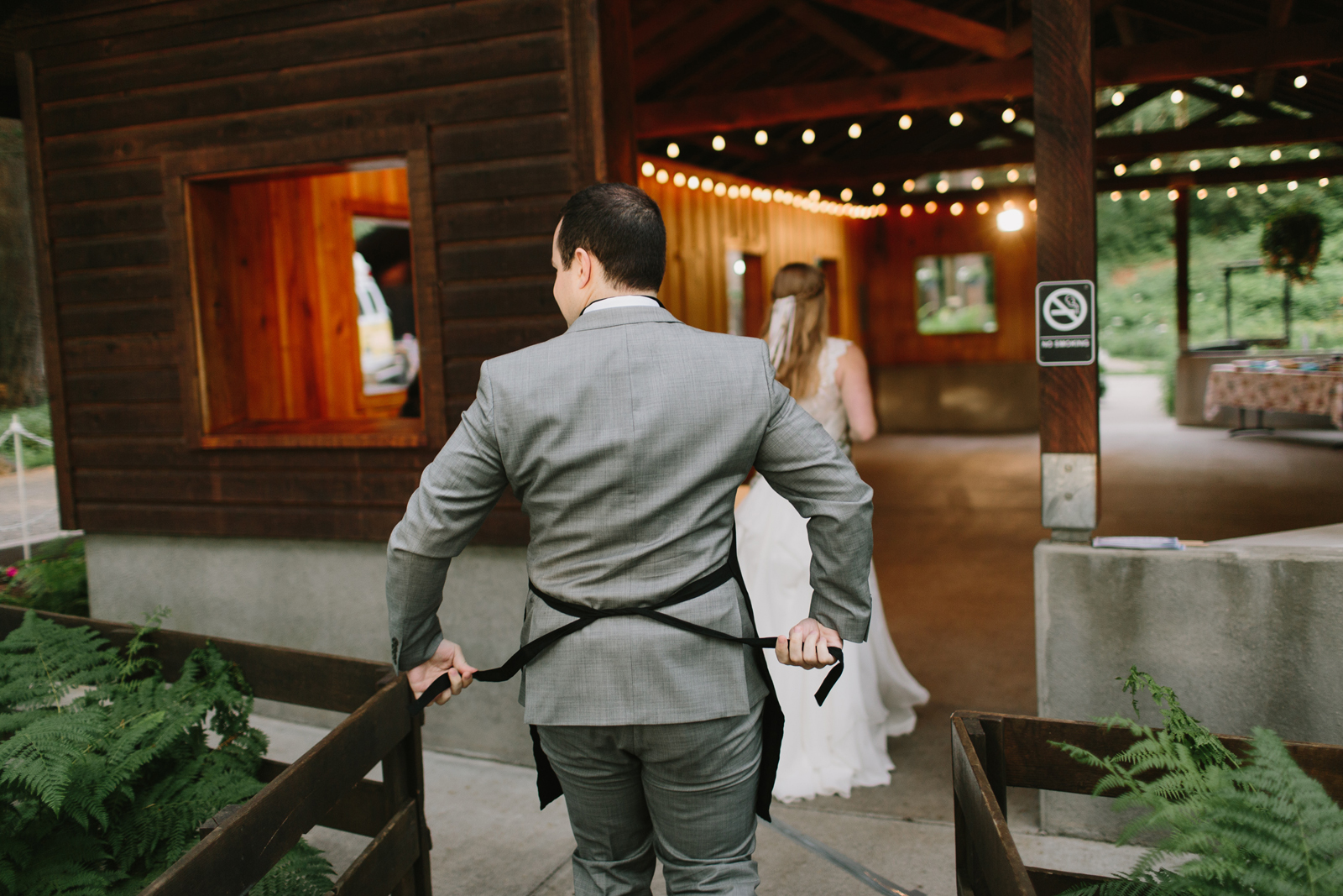 The groom adjusts his apron before cutting pies at Bridal Veil Lakes in Corbett, OR