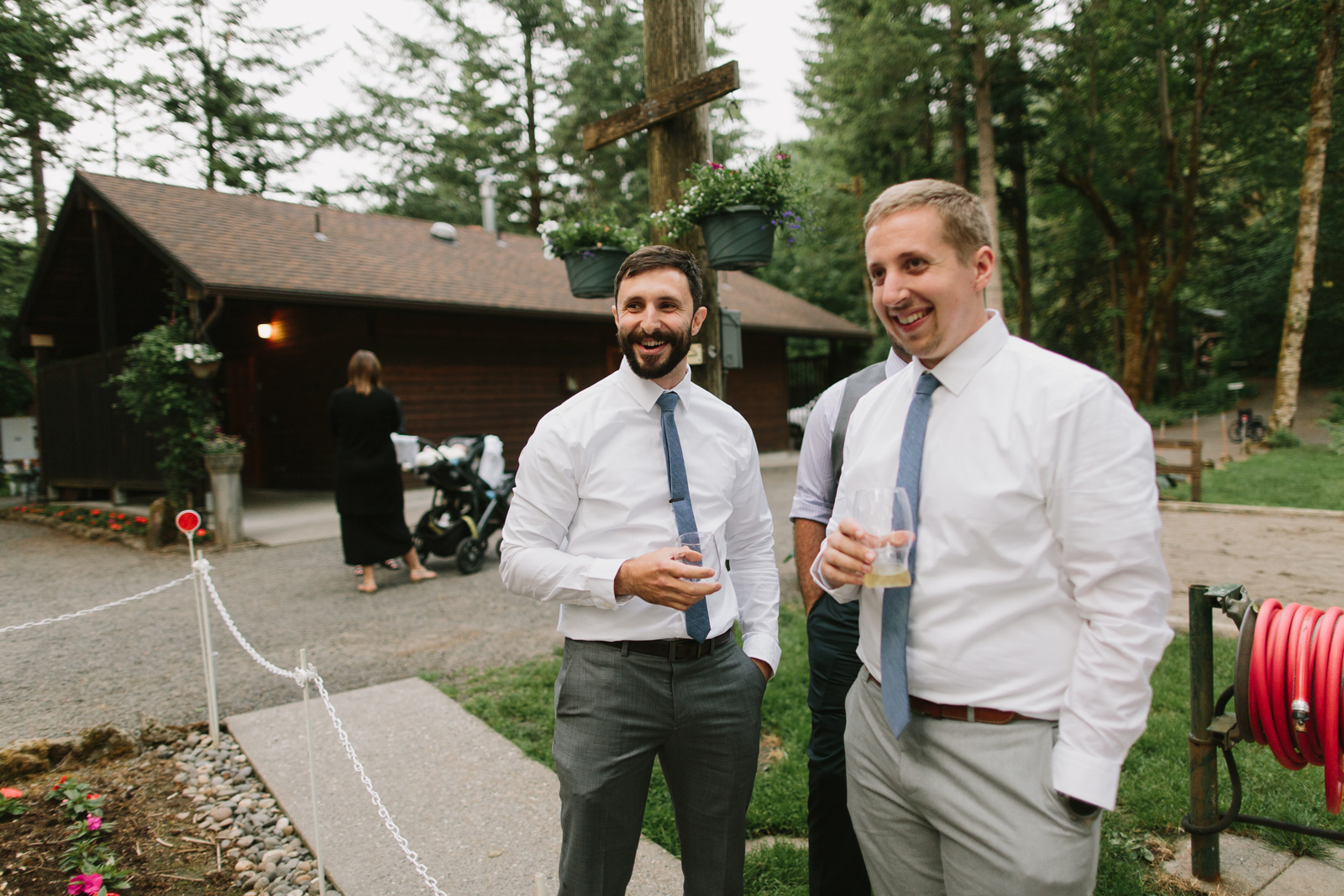 Groomsmen hang out at wedding reception at Bridal Veil Lakes in Corbett, Oregon