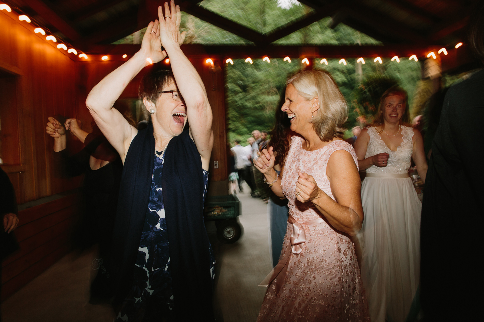 guests dance during wedding reception at Bridal Veil Lakes in Corbett, Oregon