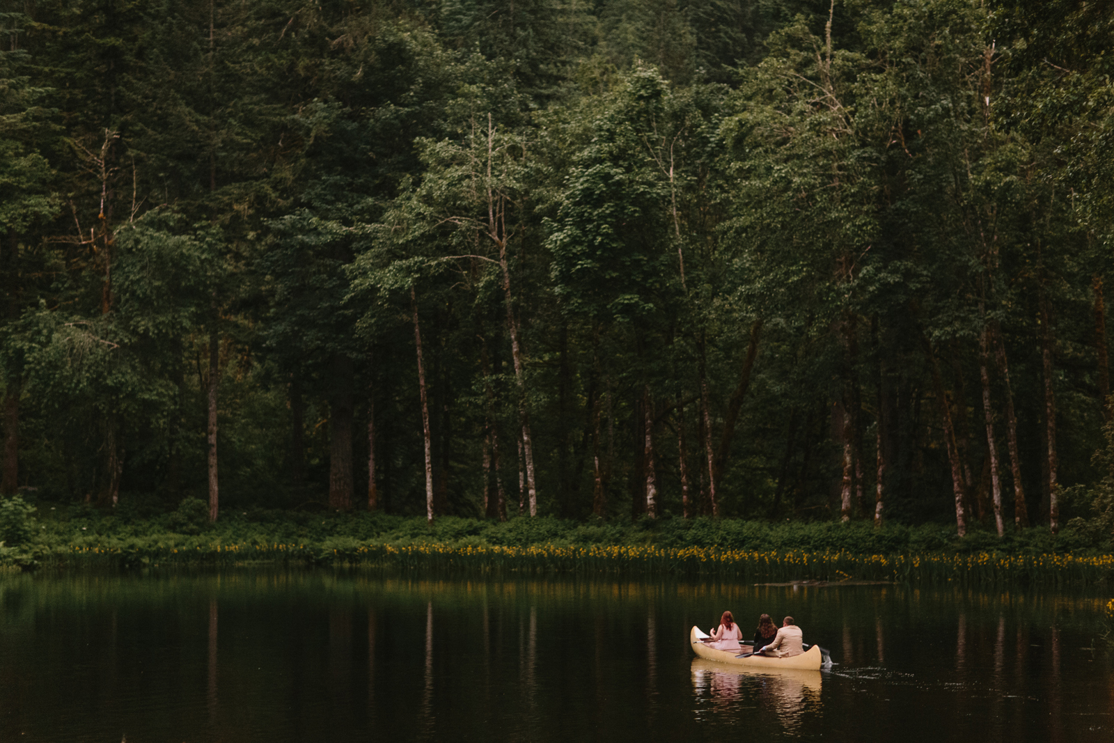 Wedding guests paddle a canoe during a wedding reception at Bridal Veil Lakes in Corbett, Oregon
