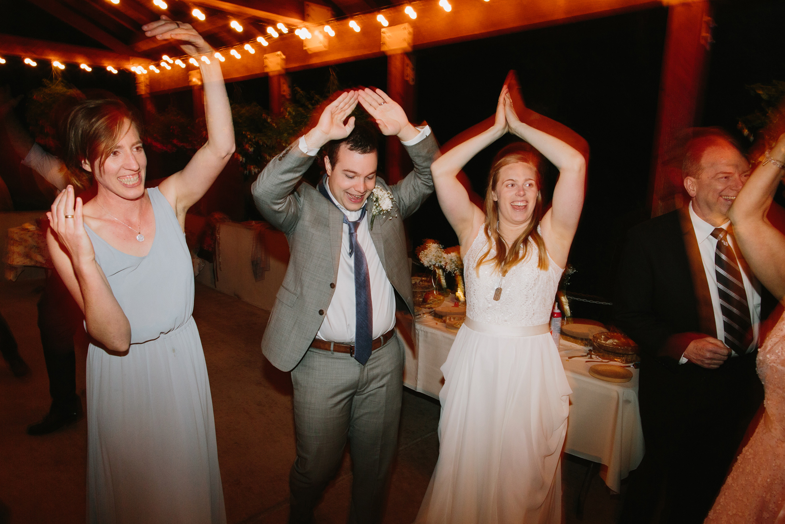 The bride and groom dance with guests during a wedding reception at Bridal Veil Lakes in Corbett, Oregon