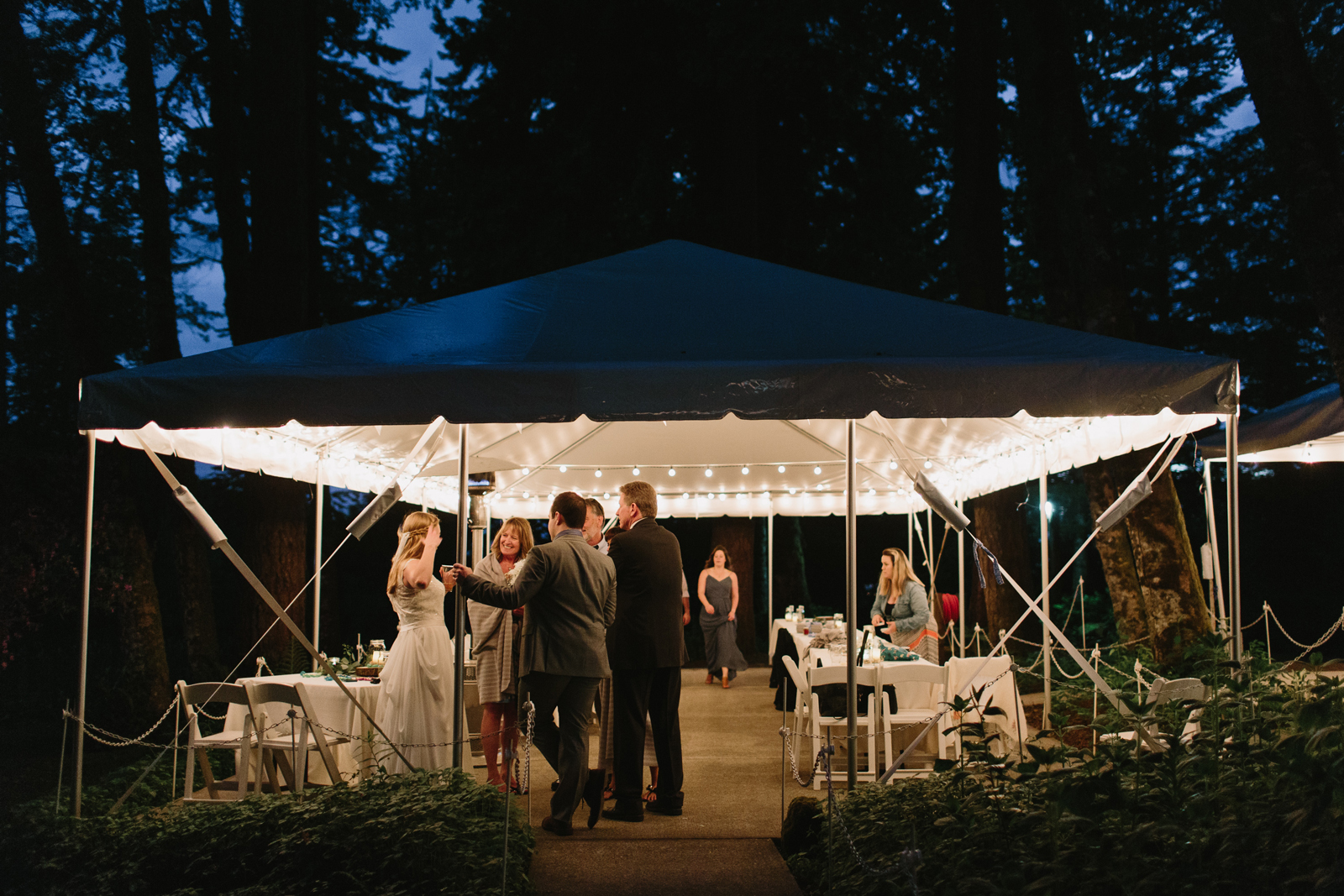 guests chat with the bride and groom during a wedding reception at Bridal Veil Lakes in Oregon