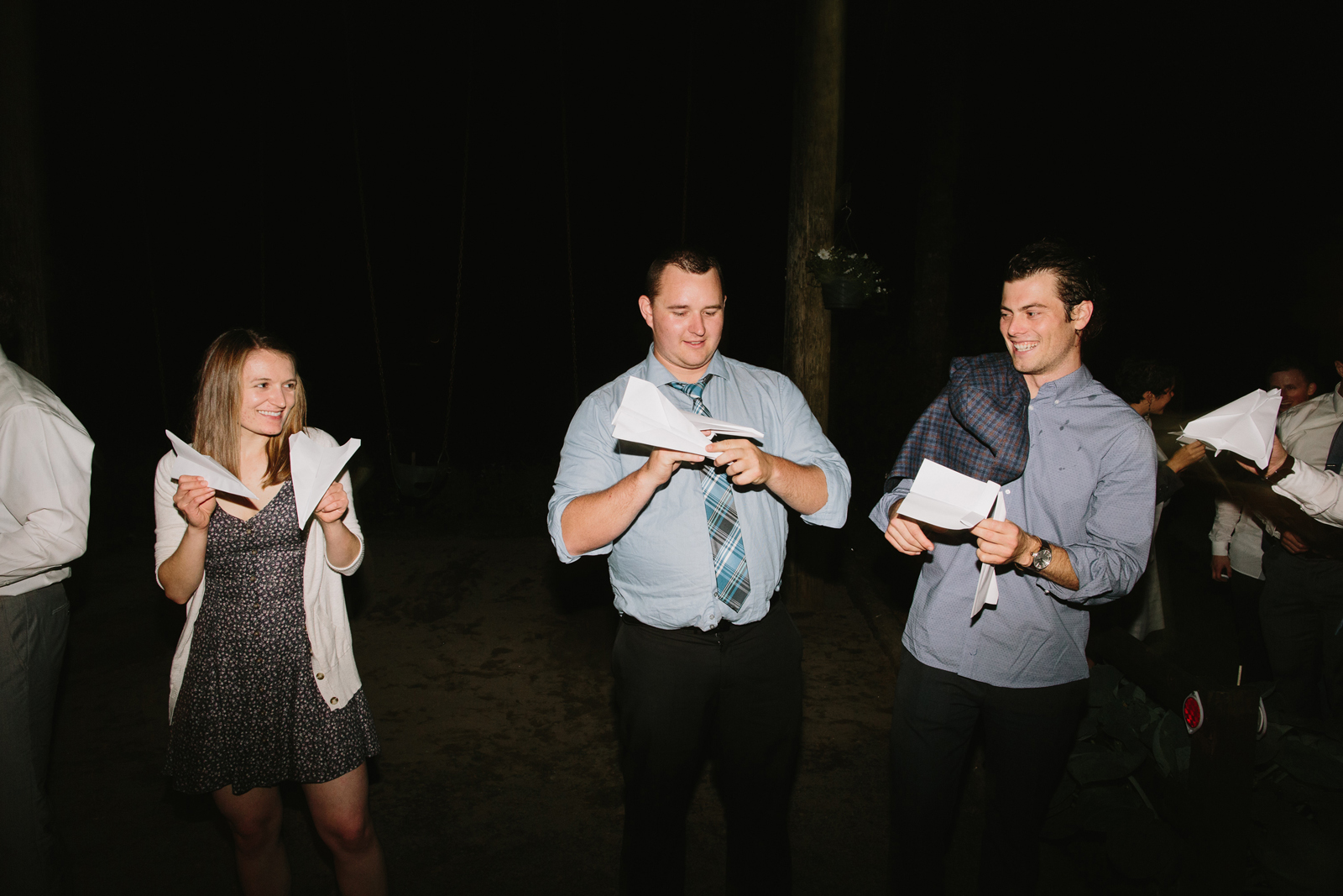 Wedding guests prepare their paper airplanes for the bride and groom's exit at a wedding reception at Bridal Veil Lakes in Corbett, OR