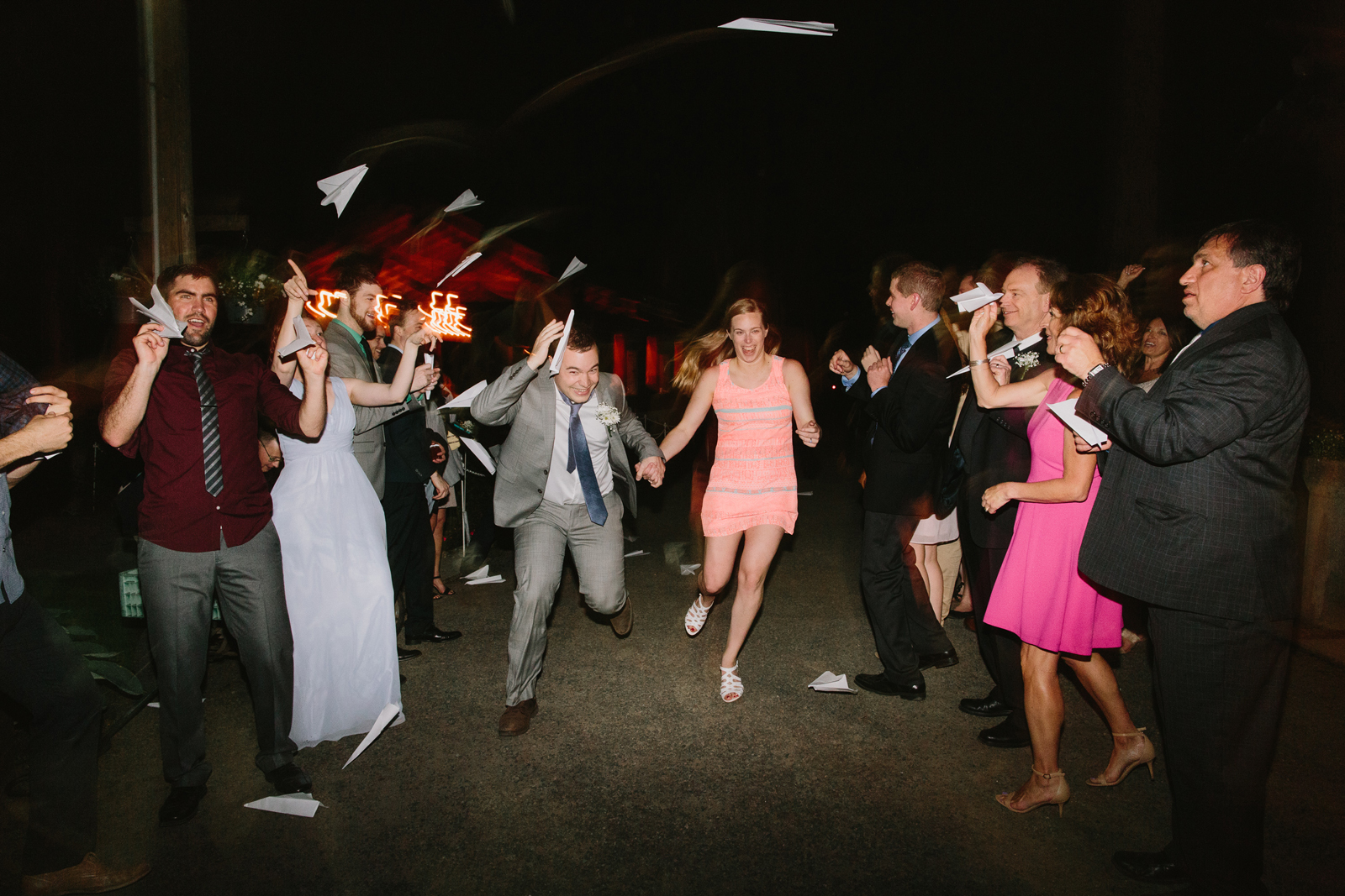 The bride and groom exit their wedding reception as guests throw paper airplanes at them during wedding reception at Bridal Veil Lakes in Corbett, OR