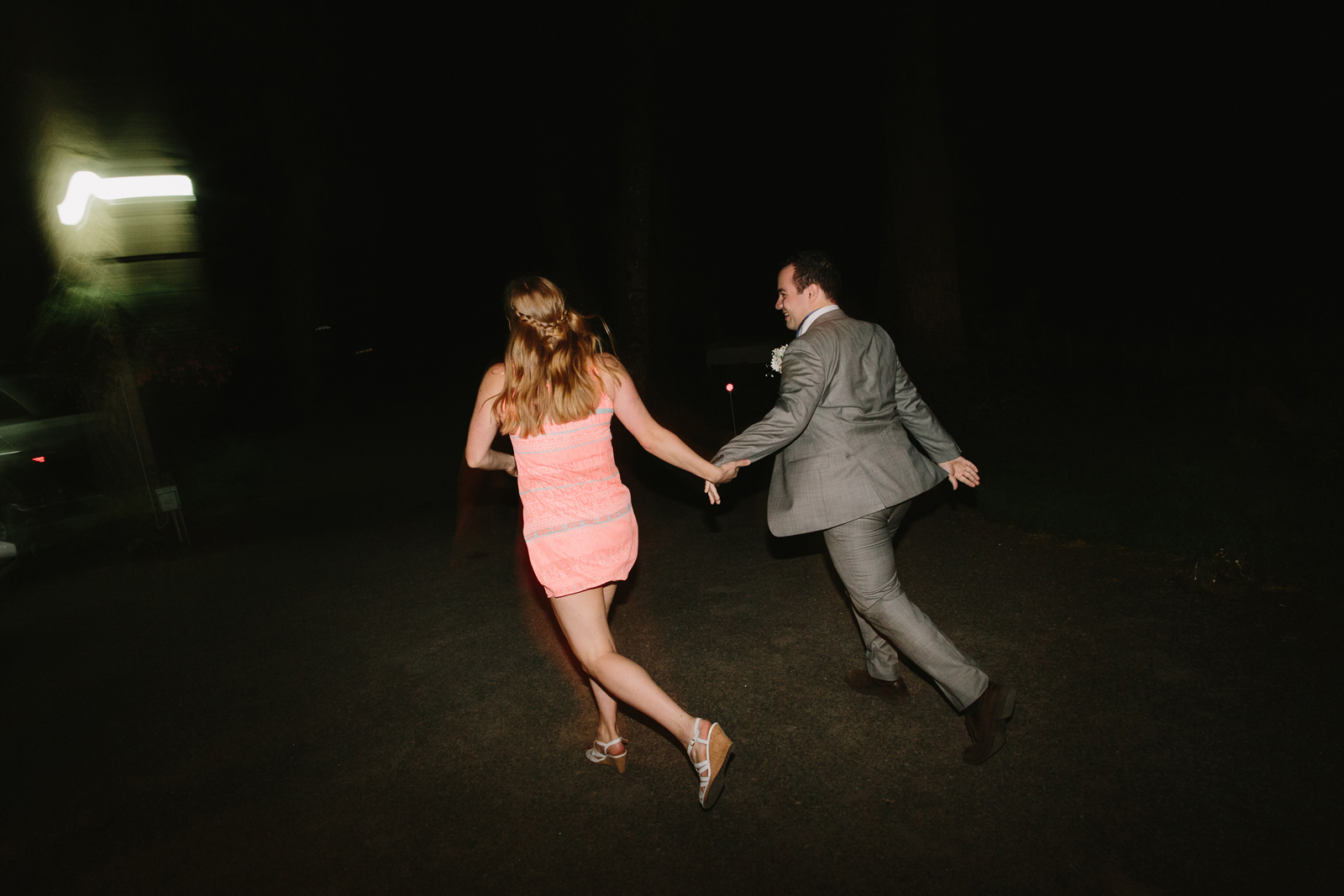The bride and groom exit their wedding reception at night at Bridal Veil Lakes in Corbett, Oregon