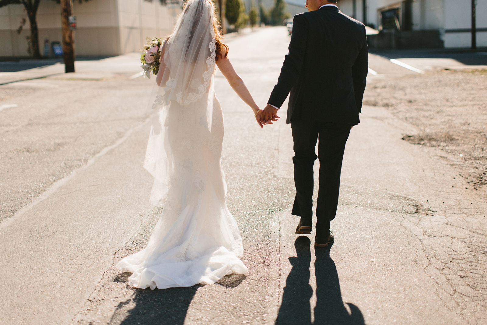 bride and groom walking in the Northwest Industrial District outside Castaway Portland