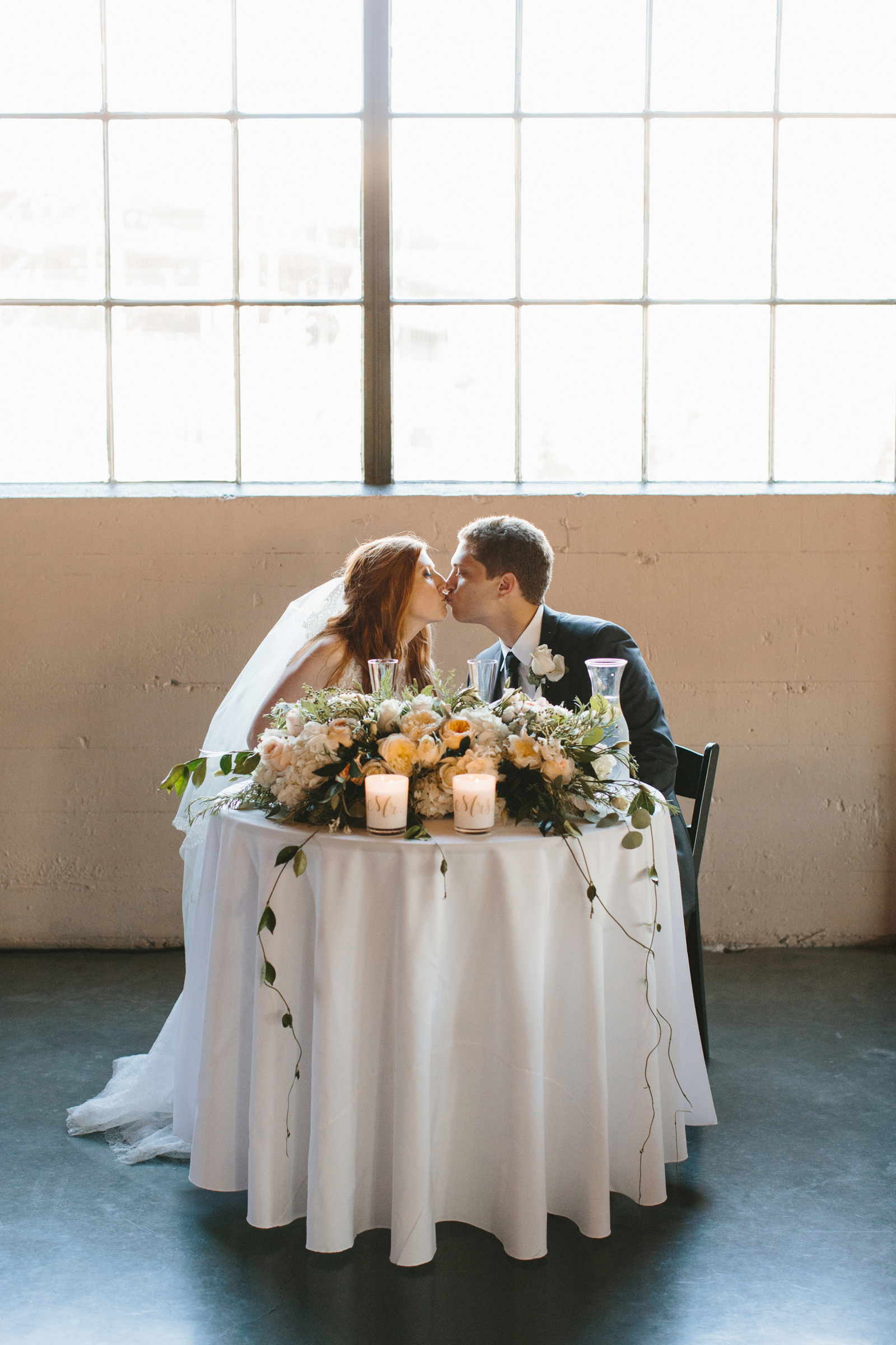 bride and groom kiss at head table at wedding reception in Northwest Portland